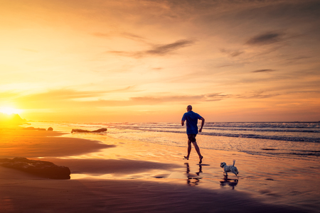 Adult man and small maltese dog are running at the beach in sunset time