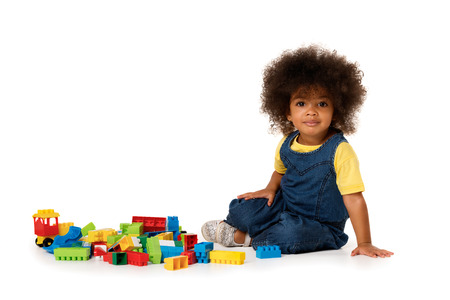 Lovely little cute african american girl on the floor with lots of colorful plastic blocks in studio, isolated on white background with copy space