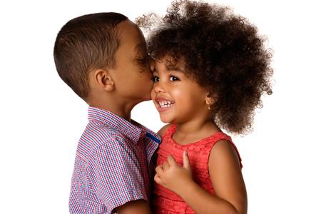 Deux frères et sœurs afro-américains joyeux, frère embrassant sa sœur, isolés sur fond blanc