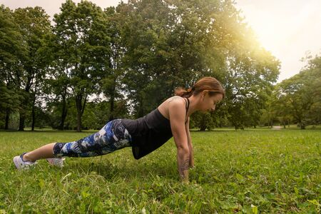 Push ups or press ups exercise by young woman, working out on grass in park