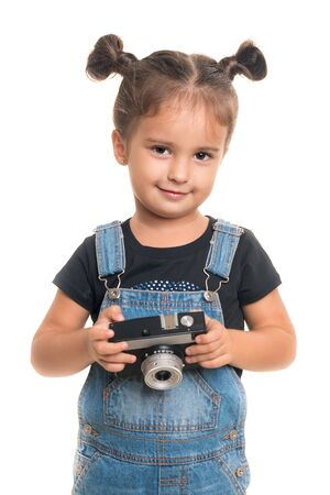 Cute and stilish baby girl  with vintage camera  posing in studio.Isolated