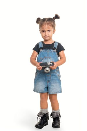 Cute and stilish baby girl  with  vintage camera  posing in studio on white background Banco de Imagens