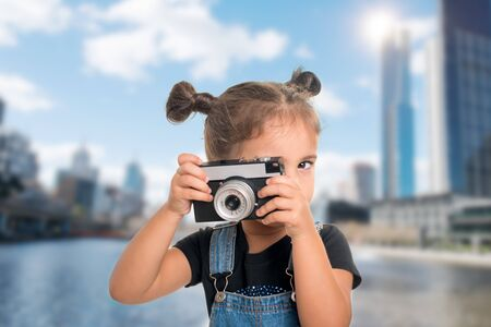 A little cute  baby girl taking a picture  with vintage camera over city background