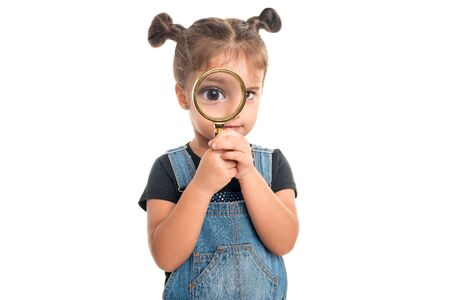 Cute baby girl  looking  through a magnifying glass.Isolated Banco de Imagens