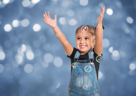 Cute little happy girl playing with bubbles over blue background Stockfoto