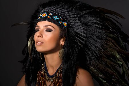 Portrait of young beautiful woman in costume of American Indian with closed eyes.Studio shot.