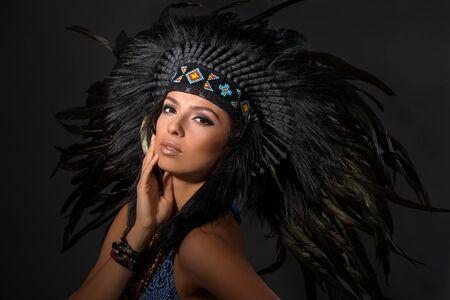Portrait of young beautiful woman in costume of American Indian.Studio shot. Stock fotó