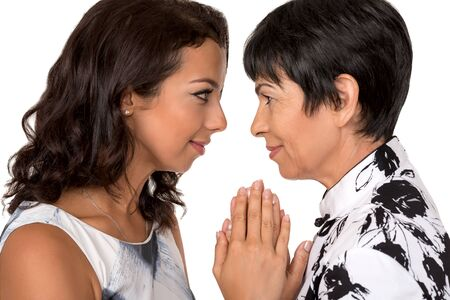 Portrait of happy mother and young daughter in profile  on white background.Family relationship, love, affection.