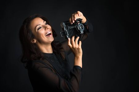 Beautiful brunette woman laughing and holding  vintage camera  on dark background Banco de Imagens
