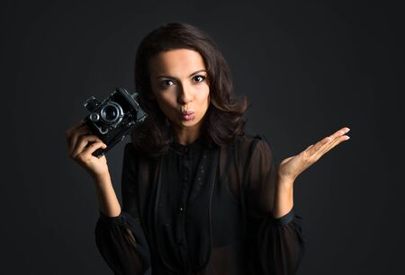Beautiful brunette woman holding  vintage camera on dark background Banco de Imagens