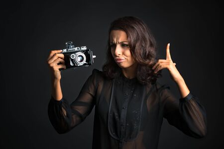 Thinking beautiful brunette woman looking at   vintage camera on dark background Banco de Imagens