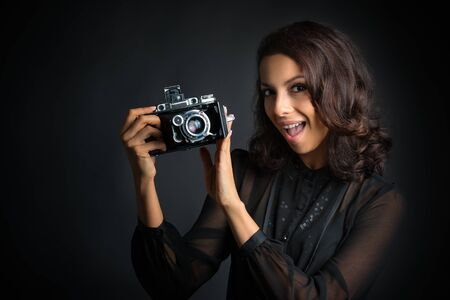 Beautiful brunette woman holding  vintage camera with open mouth on dark background
