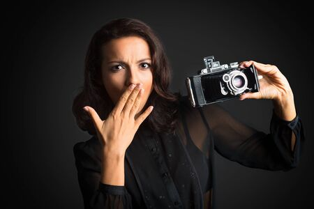 Beautiful brunette surprised woman holding  vintage camera on dark background Banco de Imagens