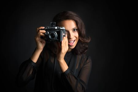 Beautiful brunette woman taking a photo by  vintage camera with happy face  on dark background Banco de Imagens