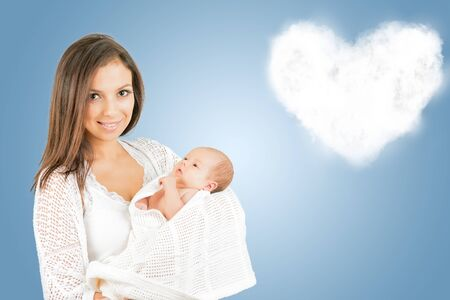 Portrait of  mother with newborn baby  with heartshaped cloud background copy space