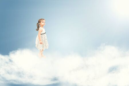 Cute little girl standing barefoot on  clouds