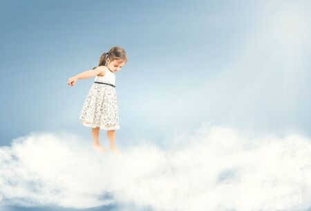Cute little girl standing barefoot and watching down on clouds