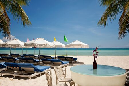 Relax area on the beach with umbrellas from sunlight and palms. Holiday, travel,vacation concept