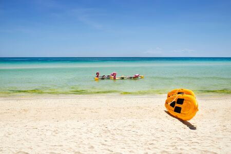 yellow paddle boards and children boats on tropical beach with white sand