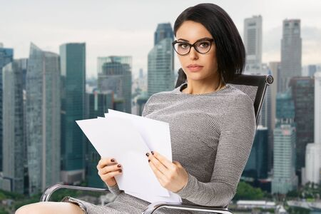 Pensive young business woman in glasses sitting on chair with paper documents over Singapore city background. .Achievement business career concept. Stock fotó