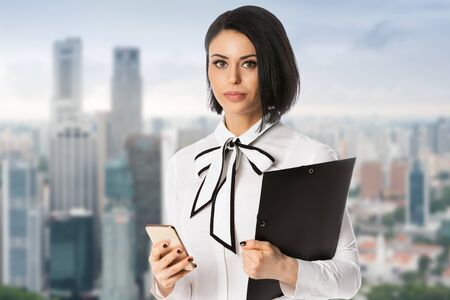 Business woman holding phone and black folder with documents in hands over city background. Concept of leadership and success