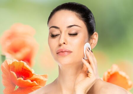 Beautiful brunette woman with cotton pad over flowered background. Beauty skin care concept. Banque d'images