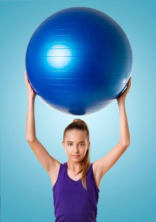 Fitness woman holding exercise ball during workout. Beautiful smiling happy caucasian fit female fitness woman over blue background.