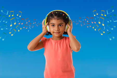 Music, childhood and technology concept- little indian girl with headphones over blue color backgroundound with musical notes