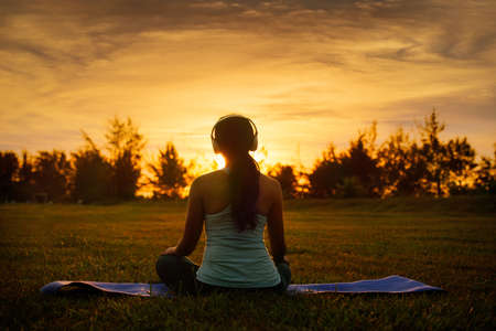 Concept of healthy lifestyle and relaxation-back view of attractive girl in sportswear with headset sitting in lotus position while listening the music outdoor on sunset