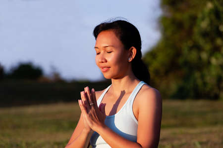 people, fitness, sport and healthy lifestyle concept - close up portrait of thoughtful pensive beautiful charming asian woman making yoga meditation outdoor Standard-Bild