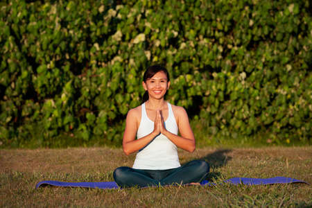 people, fitness, sport and healthy lifestyle concept-sportive thoughtful pensive beautiful charming asian woman with close eyes practicing yoga outdoor in the park