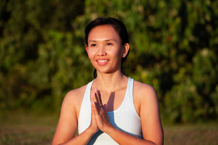 people, fitness, sport and healthy lifestyle concept - close up young smiling asian girl making yoga pose hands together outdoor Standard-Bild