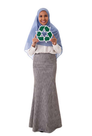 environment, eco living and sustainability concept - full length portrait of happy smiling young asian muslim woman holding green recycling sign isolated over white background Standard-Bild