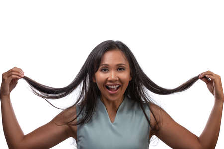 Lifestyle, emotions and happiness concept - cheerful beautiful asian woman pulling her long hair isolated over white background Standard-Bild