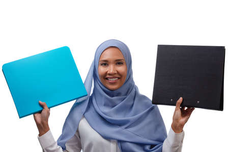 portrait of young smiling asian muslim business woman in blue hijab holding two document folders isolated over white background