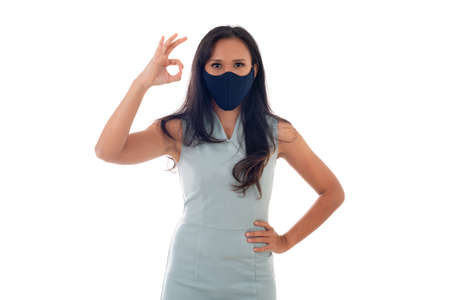 Flu epidemic, dust allergy, protection against virus concept- studio portrait of young asian woman wearing a face mask and showing ok sign with fingers, isolated on white background