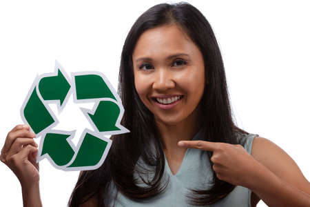 environment, eco living and sustainability concept - close up portrait of portrait of happy smiling young asian woman pointing finger to the green recycling sign isolated over white background