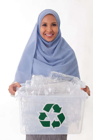 eco living and environment concept - happy smiling young asian muslim woman in hijab holding plastic garbage in plastic box isolated over white background Standard-Bild