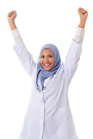 medicine, healthcare, charity and people concept -happy cheerful muslim woman nurse/doctor with arms up. Young mixed-race Asian / Caucasian female medical professional. Isolated on white background Standard-Bild