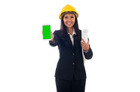 portrait of mixed race asian/caucasian engineer woman with helmet holding blueprints and showing green screen mobile phone isolated white background Standard-Bild