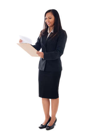 Full length of a smiling young businesswoman in suit holding documents isolated over white background