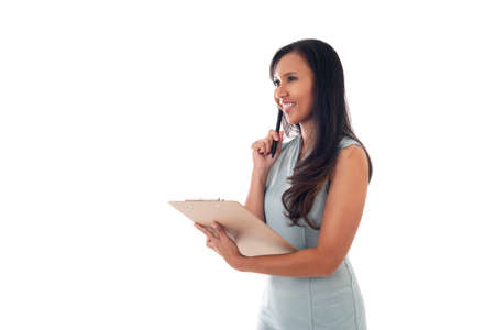 Portrait of a smiling mixed race asian/caucasian woman holding documents with pen while looking up isolated over white background