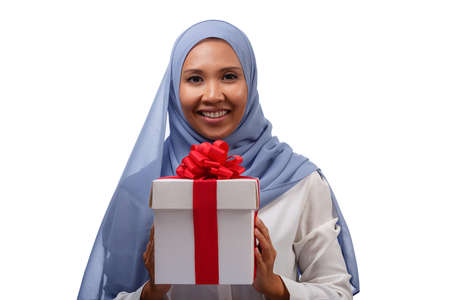 Close up portrait of happy young asian muslim woman in blue hijab holding gift box with ribbon isolated over white background Standard-Bild