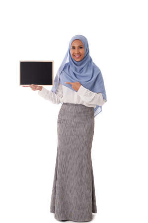 full length portrait of young asian muslim woman in hijab pointing finger towards the chalkboard isolated over white background