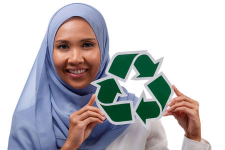environment, eco living and sustainability concept - close up portrait of happy smiling young asian muslim woman holding green recycling sign isolated over white background.
