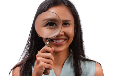 close up portrait of young smiling mixed race asian-caucasian woman with magnifying glass. Isolated on white background.