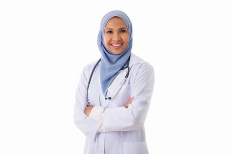 medicine, healthcare, charity and people concept - smiling muslim female doctor wearing hijab and white coat standing with crossed arms over white background. Standard-Bild