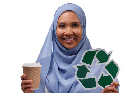 environment, eco living and sustainability concept - close up portrait of happy smiling young asian muslim woman holding green recycling sign and takeaway paper coffee cup isolated over white background. Standard-Bild