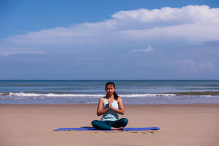 people, fitness, sport and healthy lifestyle concept - young asian woman making meditation on tropical beach with blue sky background