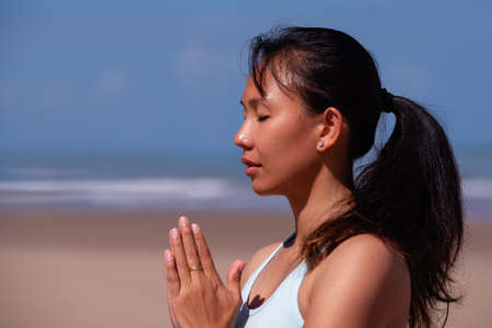 people, fitness, sport and healthy lifestyle concept - close up portrait of young asian woman making meditation on tropical beach with blue sky background
